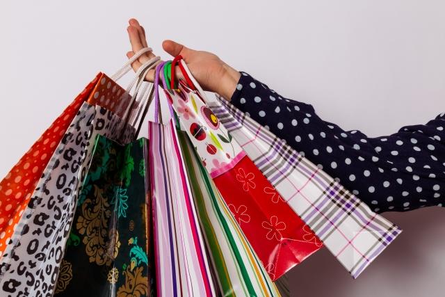 買い物の紙袋を持つ手