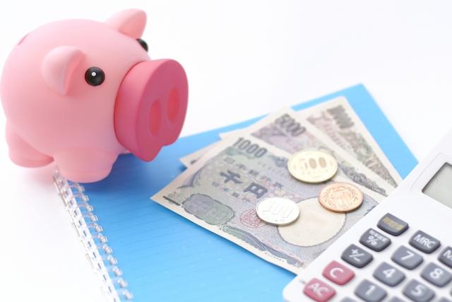 ブタの貯金箱とお金と電卓